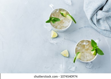 Food and drink, holidays party concept. Cold fresh classic beverage moscow mule cocktail in a silver mug with vodka, ginger beer. lime and mint for refreshment in summer days. Top view copy space