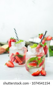 Food and drink, holidays party concept. Cold fresh alcohol beverage mojito cocktail with white rum, soda, red strawberry and basil for refreshment in summer days. Copy space background