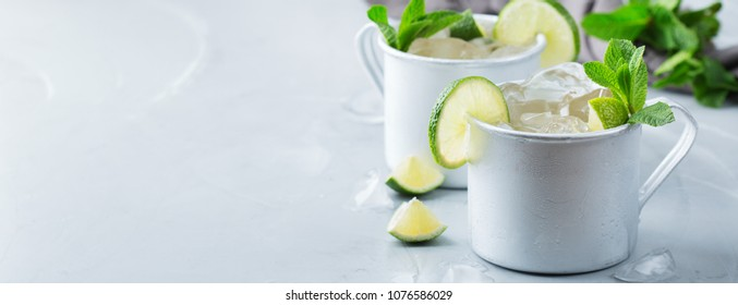 Food and drink, holidays party concept. Cold fresh classic beverage moscow mule cocktail in a silver mug with vodka, ginger beer. lime and mint for refreshment in summer days. Copy space background