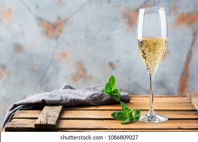 Food and drink, holidays party concept. Cold fresh alcohol beverage champagne sparkling white wine with bubbles in a flute glass on a wooden table. Copy space background