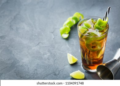 Food and drink, holidays party concept. Alcohol cocktail with rum and cola cuba libre beverage, longdrink in a glass with straw, ice and lime zest on a dark table. Copy space top view background