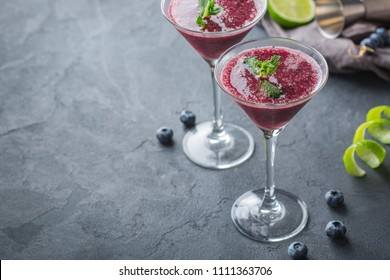 Food and drink, holidays party concept. Cold fresh frozen blueberry beverage margarita cocktail with tequila and lime juice for refreshment in summer days
