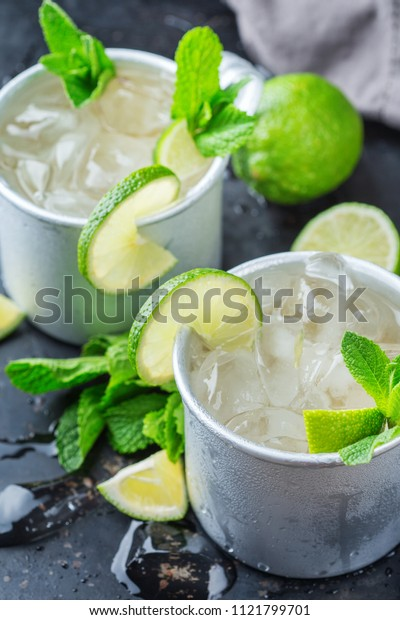 Food and drink, holidays party concept. Cold fresh classic beverage moscow mule cocktail in a silver mug with vodka, ginger beer. lime and mint for refreshment in summer days