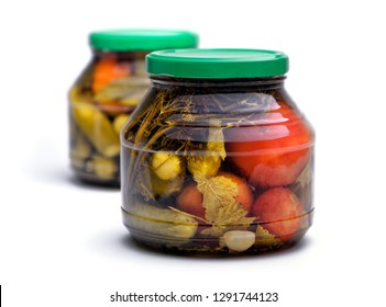 Food and drink: homemade preserves, pickled cucumbers and tomatoes in a glass jar, isolated on white background