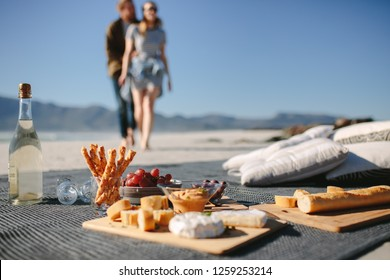 Food and drink on the blanket at the beach with couple walking towards it. Picnic setting on the beach with man and woman in background.
