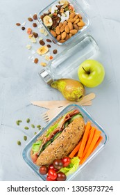Food and drink, still life, diet and nutrition, healthy eating, take away concept. Lunch box with sandwich, fruits, vegetables, nut mix and bottle of water. Top view flat lay background