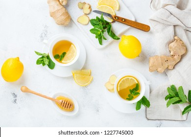 Food and drink, still life health care concept. Ginger tea infusion beverage in white cup with lemon mint honey on a kitchen table for cold and flu winter autumn days. Top view background