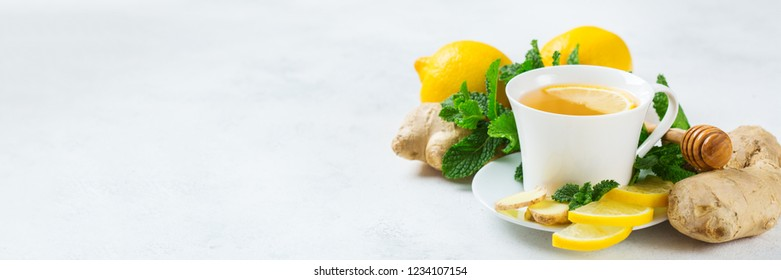 Food and drink, still life health care concept. Ginger tea infusion beverage in white cup with lemon mint honey on a kitchen table for cold and flu winter autumn days. Copy space background