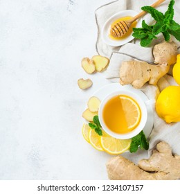 Food and drink, still life health care concept. Ginger tea infusion beverage in white cup with lemon mint honey on a kitchen table for cold and flu winter autumn days. Top view copy space background