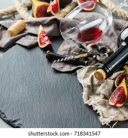 Food and drink, still life, holidays seasonal harvesting fall autumn concept. Bottle, corkscrew, corks, glass of red wine and figs on a grunge table. Copy space background