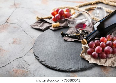 Food and drink, still life, holidays seasonal harvesting fall autumn concept. Bottle, corkscrew, corks, glass of red wine and grapes on a grunge table. Copy space background