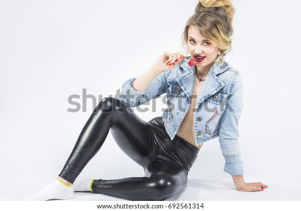 Food and Drinks Ideas. Closeup Portrait of Caucasian Blond Girl Eating Red Lollipop on Stick. Posing in Latex Pants and Jeans Jacket. Horizontal Image Composition