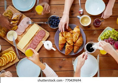 food, eating and family concept - group of people having breakfast and sitting at table