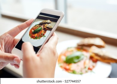 food, eating, technology, culinary and people concept - woman hands with gazpacho soup photo on smartphone screen at restaurant