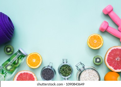 Food for fitness, healthy lifestyle frame flatlay with fat burning fruits orange and grapefruits slices, complex carbohydrates, detox water bottle, violet yoga mat, pink hand weights, green background