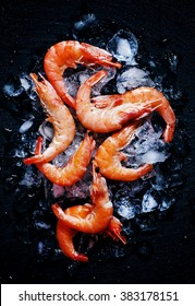 Food flat background, shrimp and ice on dark stone, top view