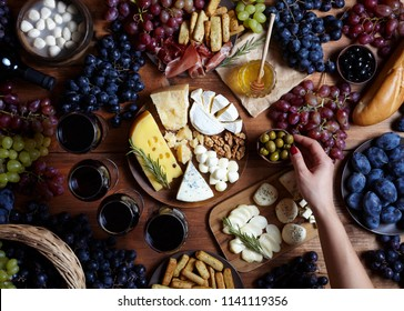 Food flat lay. Cheese plate served with wine, grapes, prosciutto, olives, snack table, jam and honey. Top view