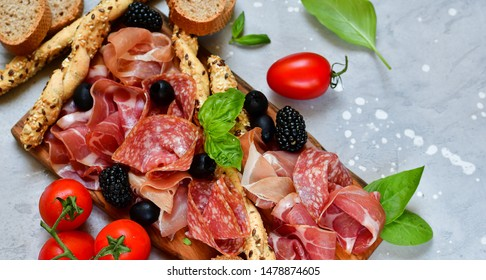 food flat lay italian  antipasti prosciutto, salami, bresaola olives tomatoes and grissini bread sticks. aperitif happy hour