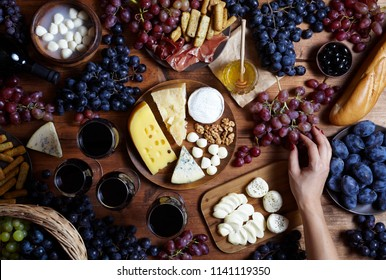 Food flat lay. Overhead of cheese plates served with grapes, honey, crackers and nuts on a wooden background, Top view. Camembert, mozzarella, parmesan cheeseboard. Festive table with snacks.