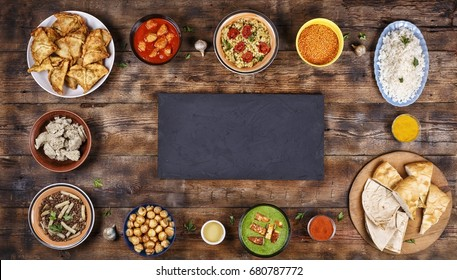 Food frame. Assorted indian food on a wooden. Dishes, appetizers of indian cuisine. Curry, butter chicken, rice, lentils, palak paneer, samosa, naan, chutney, spices. Bowls and plates with indian food