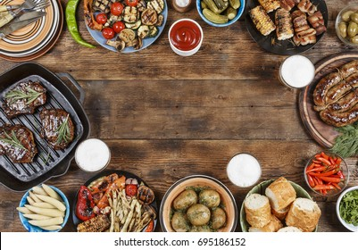 Food frame. Different foods cooked on the grill on the wooden table with copy space, grilled steak, grilled sausage and grilled vegetables. Top view