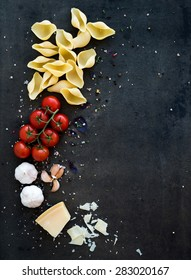 Food frame. Pasta ingredients. Cherry-tomatoes, pasta, garlic, basil, parmesan and spices on dark grunge backdrop, copy space, top view