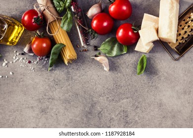 Food frame. raw Pasta ingredients. Cherry-tomatoes, spaghetti pasta, garlic, basil, parmesan and spices on dark grunge backdrop, copy space, top view