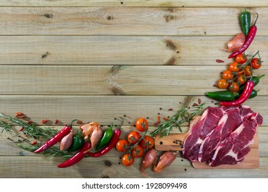 Food frame of raw veal, fresh vegetables and greens with place for text