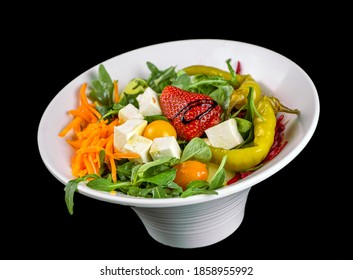 FOOD - Fresh mixed salad with cheese and strawberry, green peppers, jalapeño, rucula. carrot and beet, in a withe stylish dish. Black background.