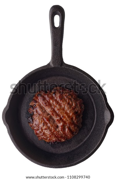 Food: fried homemade burger on a frying pan, isolated on white background