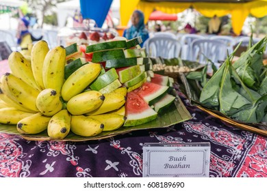 Food and fruits on display on the table at a gathering event, with a sign card 'buah-buahan', means fruits[[[[-