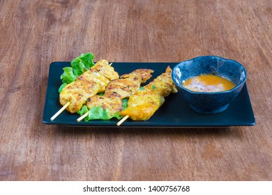 Thaï Food: Gai Satay, chicken skewers with peanut sauce, served on a wooden table.