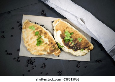 Food: Georgian cuisine. Vegan lobiani stuffed with beans and parsley. Khachapuri: bean-filled bread. Vegetarian delicacy with onions. Food on a black background