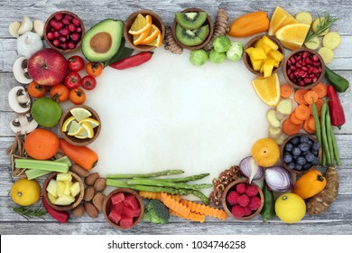 Food for good health and fitness background border with fresh vegetables, fruit, herbs, spices and nuts. Super foods concept high in antioxidants, anthocyanins, fibre and vitamins.