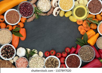 Food for good health and fitness background border with fresh vegetables, legumes, herbs, spice, cereals, oil and seeds on slate background.  High in antioxidants, anthocyanins, minerals and vitamins.