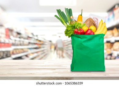 Food and groceries in green eco-friendly reusable shopping bag on wood table with blurred suppermarket aisle in background