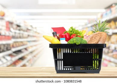 Food and groceries in shopping basket on wood table with blurred suppermarket aisle in background