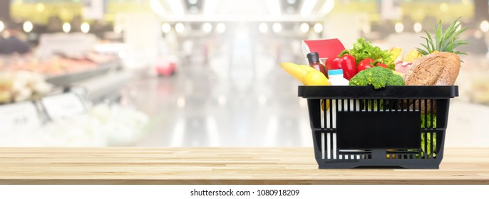 Food and groceries in shopping basket on wood table with blurred suppermarket in background, panoramic banner with copy space