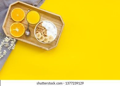 food for healthy breakfast with granola and fresh orange juice on bright yellow background top view mock up