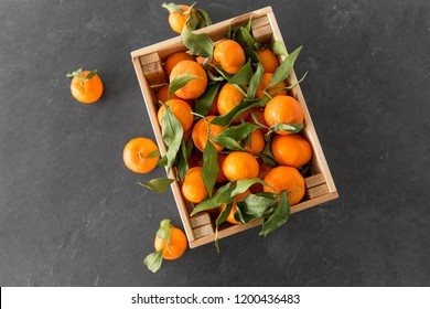 food, healthy eating and vegetarian concept - close up of whole mandarins with leaves on slate table top