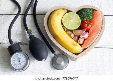 Food and healthy heart diet concept with blood preasure guage on white planks