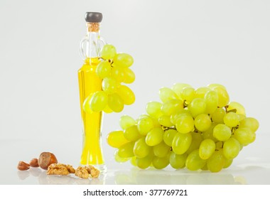 Food for healthy life: bottle of natural oil, bunch of grapes and nuts on neutral background