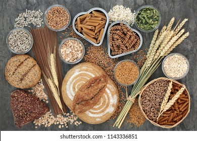 Food high in dietary fibre with whole grain bread and seeded rolls, whole wheat pasta, seeds, cereals and grains on marble background top view. Foods high in antioxidants, omega 3 and vitamins.