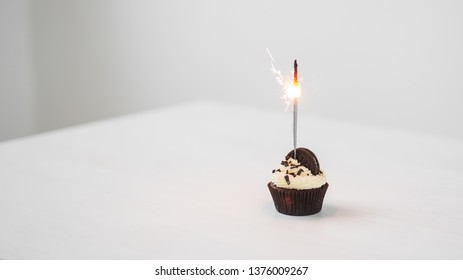 Food and holiday concept - Birthday cupcake with sparkler over white background with copy space