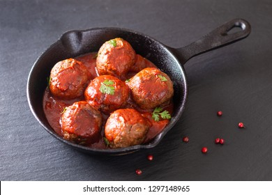 Food Homemade organic spicy meatball in iron cast on black slate stone background