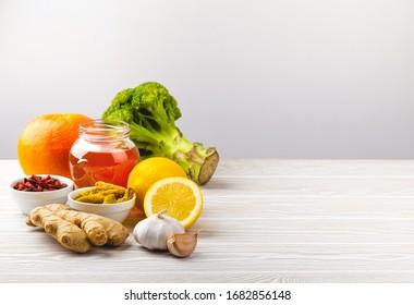 Nourriture pour la stimulation de l'immunité et protection contre les virus. Brocoli, agrumes, miel, gingembre, citron, ail, goji, curcuma sur fond blanc bois, espace pour copie. Une alimentation saine pour renforcer le système immunitaire