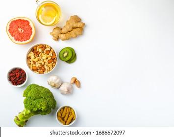 Nourriture pour la stimulation de l'immunité et protection contre les virus. Brocoli, agrumes, miel, gingembre, citron, ail, goji, curcuma sur fond blanc, espace pour texte. Une alimentation saine pour renforcer le système immunitaire