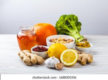 Nourriture pour la stimulation de l'immunité et protection contre les virus. Brocoli, agrumes, miel, gingembre, citron, ail, goji, curcuma sur fond blanc bois. Aliments naturels sains pour renforcer le système immunitaire