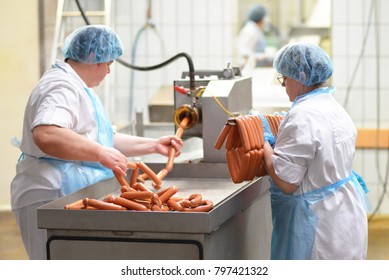 food industry: workers in the production of original German bratwurst in a large butcher's shop