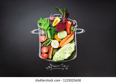 Food ingredients for blending creamy soup on painted stewpan over black chalkboard. Top view with copy space. Organic vegetables, spices, herbs. Vegetarian, vegan, detox, clean eating concept.